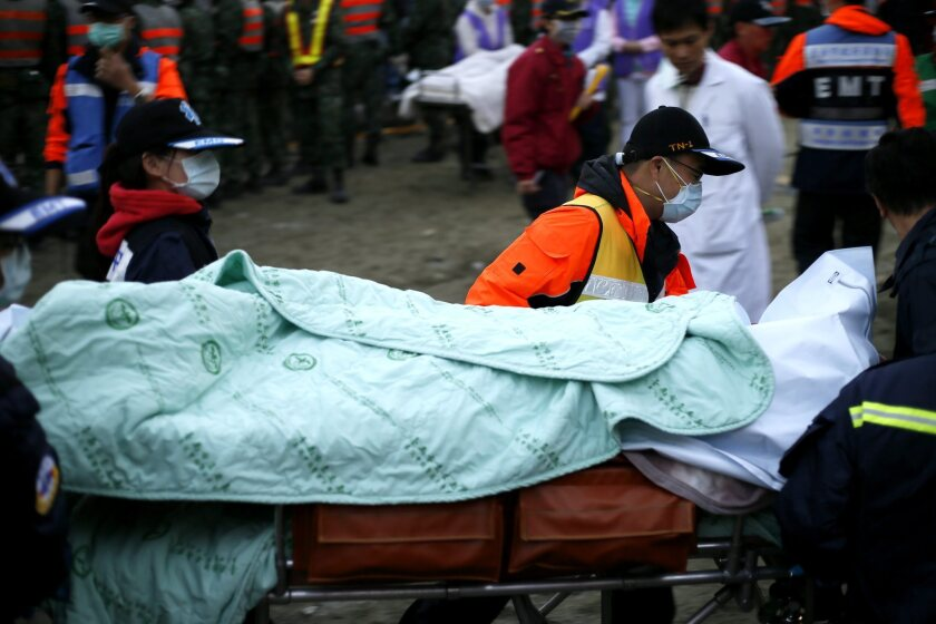 Rescuers remove a body from a collapsed building on Feb. 7 after the earthquake in Tainan, southern Taiwan.