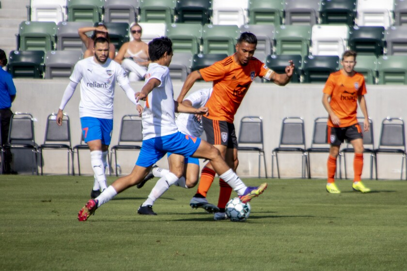 Orange County's Michael Orozco executes a tackle against a Rio Grande Valley FC player in the first half on Saturday.