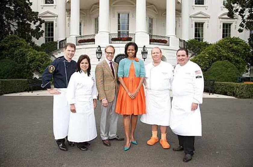 From left, chefs Bobby Flay, Cristeta Comerford, host Alton Brown, First Lady Michelle Obama and chefs Mario Batali and Emeril Lagasse