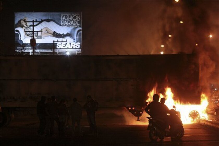 People watch as a truck blocking the road burns in the city of Morelia, Mexico Friday Nov. 5, 2010. Authorities reported a federal police operation in the historic city of Patzcuaro outside of Morelia that sparked incidents of kidnapping, vandalism and cars set afire on the road between the two cities in the western state of Michoacan, which is controlled by La Familia cartel.(AP Photo)