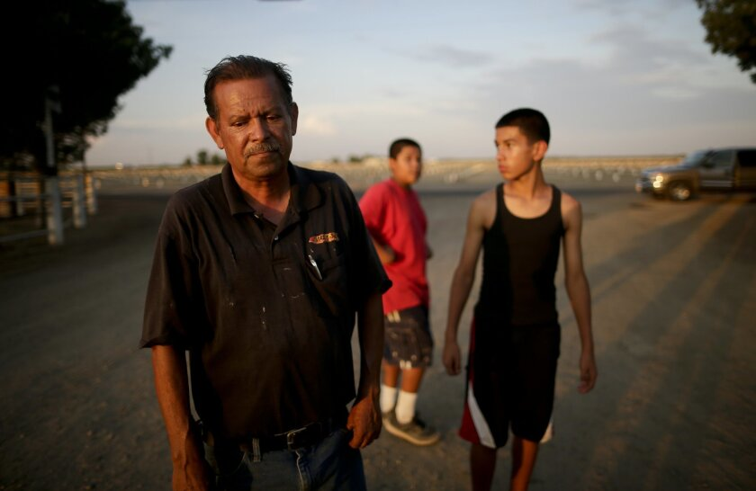 In this June 30, 2015 photo, Gilbert Arredondo, left, looks down as he talks about his town's water crisis, standing in front of his tenant's sons, in the community of Okieville, on the outskirts of Tulare, Calif. Arredondo had just informed his tenant, Tino Lozano, that the well connecting their h