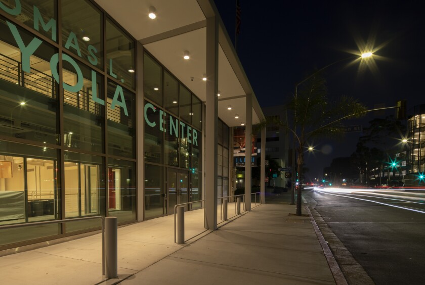 An angled view of the facade of the Beckmen YOLA Center at night illuminated from within. Traffic streams to the right.