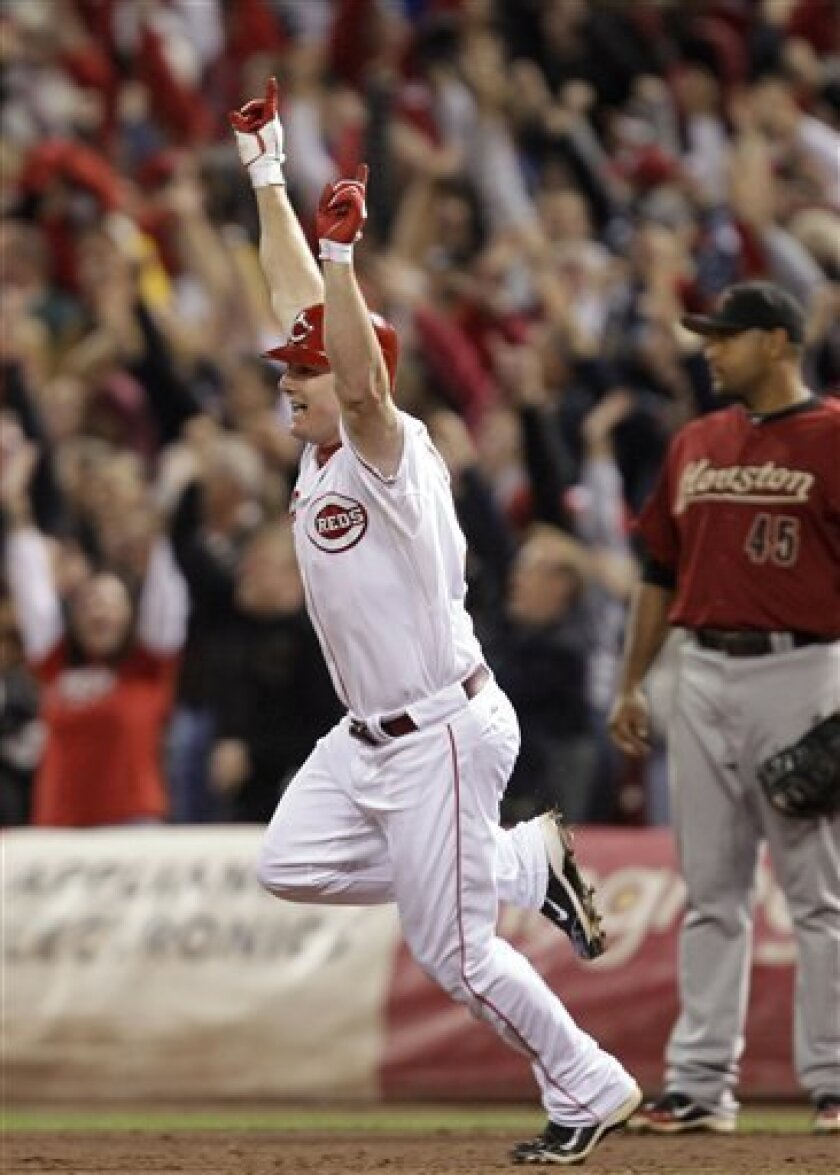Cincinnati Reds' Jay Bruce reacts after hitting a home run off Houston Astros relief pitcher Tim Byrdak in the ninth inning of a baseball game Tuesday, Sept. 28, 2010, in Cincinnati. Cincinnati clinched the NL Central with the 3-2 win. Astros first baseman Carlos Lee is at right. (AP Photo/Al Behrm