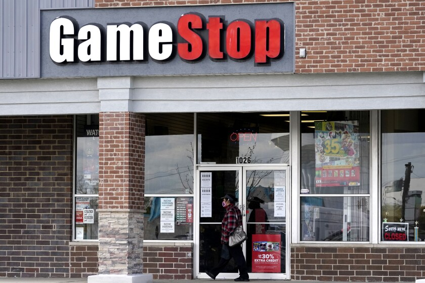 A woman wears a face mask as she walks past a GameStop store in Des Plaines, Ill., in October 2020.