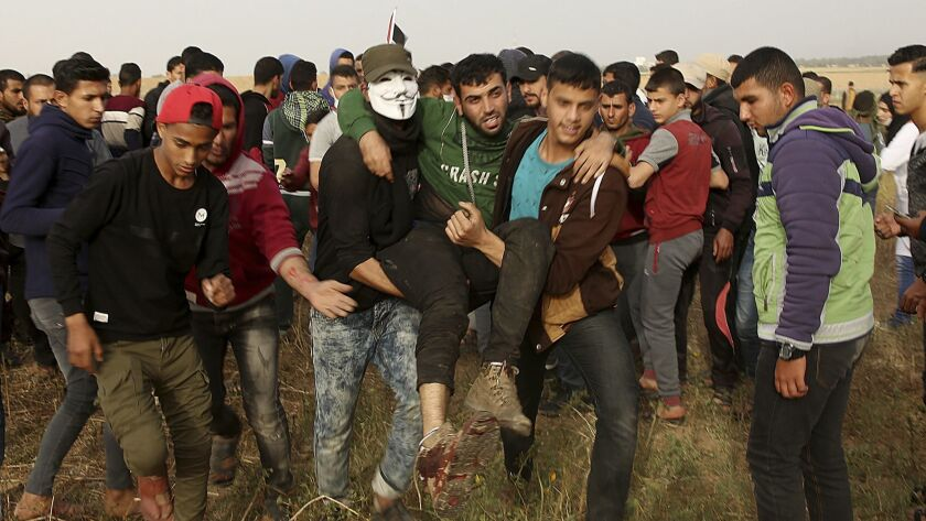 Palestinian protesters evacuate a wounded youth during clashes with Israeli troops along Gaza's bord