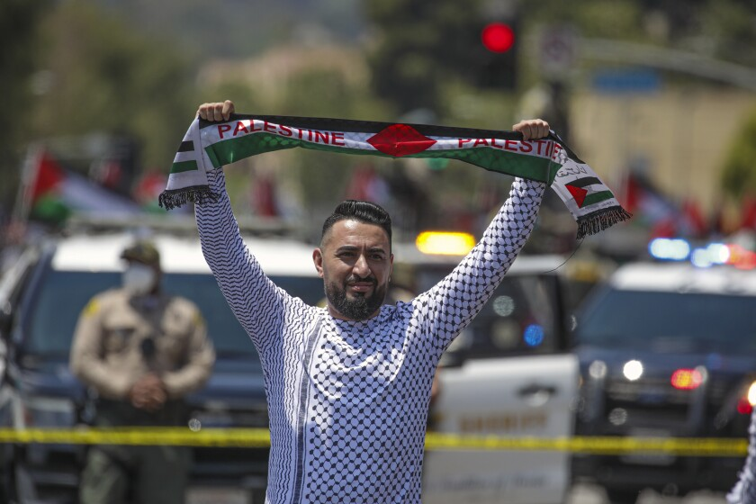 A man holds up a banner depicting the Palestinian flag, with the word Palestine