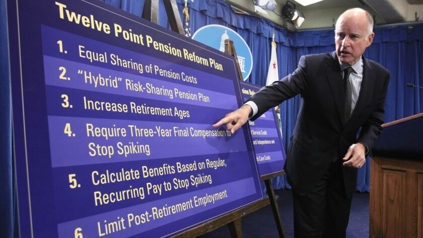 Then-Gov. Jerry Brown gestures to a chart in 2011 showing some of his proposals to roll back public employee pension benefits during a news conference at the state Capitol.