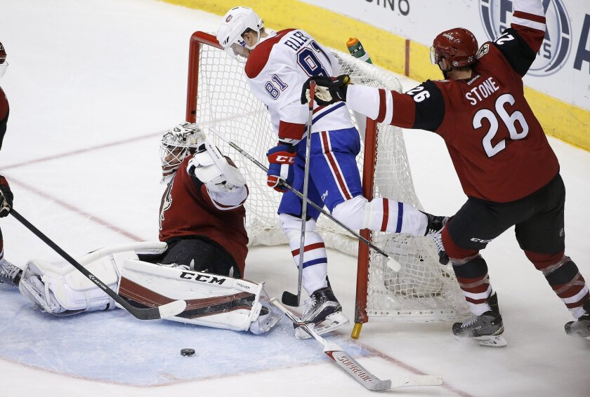 Montreal Canadiens' Lars Eller (81), of Denmark, collides with Arizona Coyotes' Louis Domingue, left, as Coyotes' Michael Stone (26) defends during the second period of an NHL hockey game Monday, Feb. 15, 2016, in Glendale, Ariz. (AP Photo/Ross D. Franklin)