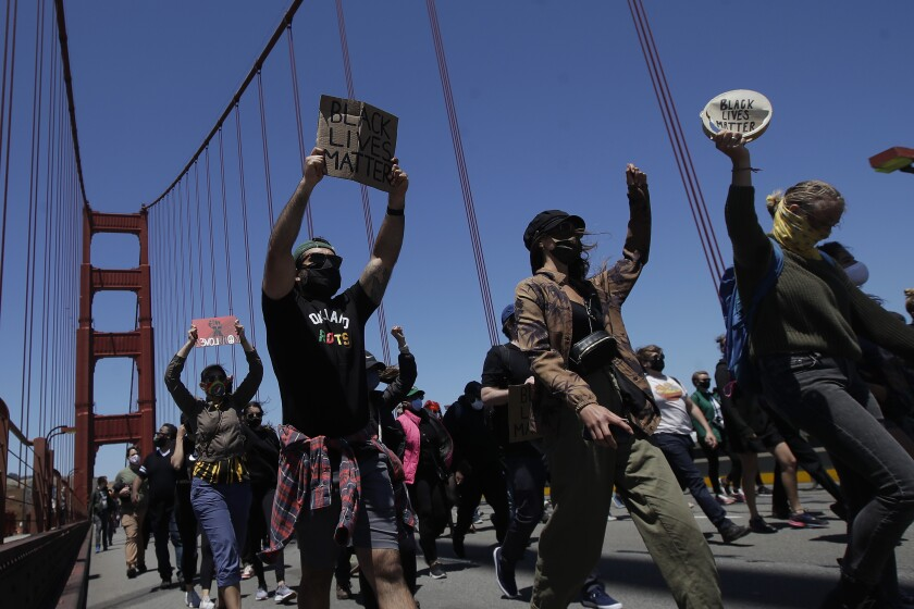 People march as traffic is stopped on the Golden Gate Bridge in San Francisco