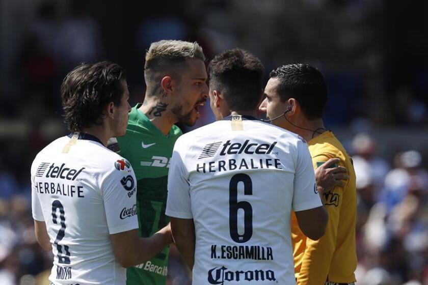 El guardameta de Pumas Alfredo Saldívar (i), reclama una jugada al arbitro central Cesar Arturo Ramos (d) ante América, durante el juego correspondiente a la jornada 7 del torneo mexicano de fútbol celebrado en el estadio Olímpico Universitario en Ciudad de México (México). EFE/Archivo