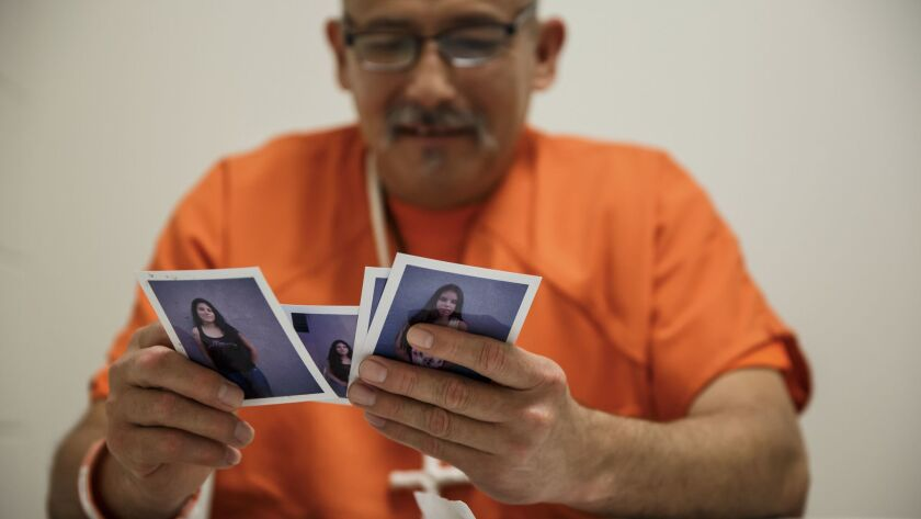 Romulo Avelica looks through family photos at the ICE detention facility in Adelanto, Calif.