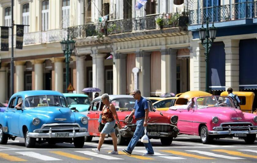 Un hombre y una mujer caminan frente a automóviles antiguos en La Habana (Cuba). EFE/Archivo