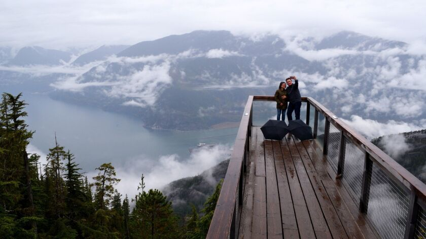 At the Sea to Sky Gondola attraction visitors take in the vistas from the Spirit Viewing Platform in Squamish, British Columbia.