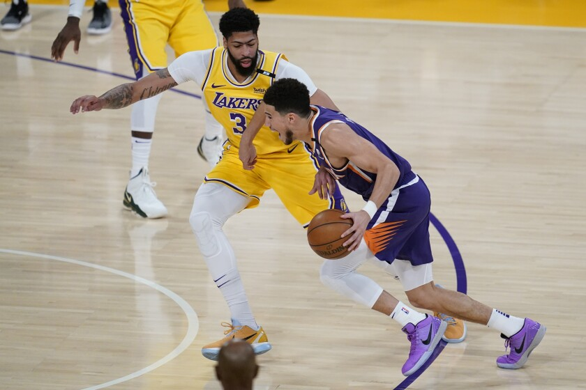 Lakers forward Anthony Davis defends as Suns guard Devin Booker drives.