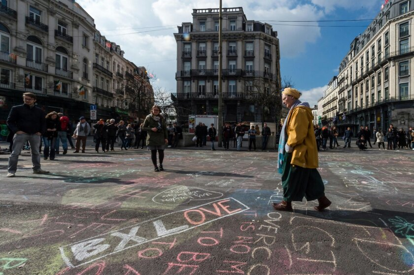 A man walks by solidarity messages written in chalk outside the stock exchange in Brussels on Tuesday, March 22, 2016. Explosions, at least one likely caused by a suicide bomber, rocked the Brussels airport and subway system Tuesday, prompting a lockdown of the Belgian capital and heightened security across Europe. At least 26 people were reported dead. (AP Photo/Geert Vanden Wijngaert)