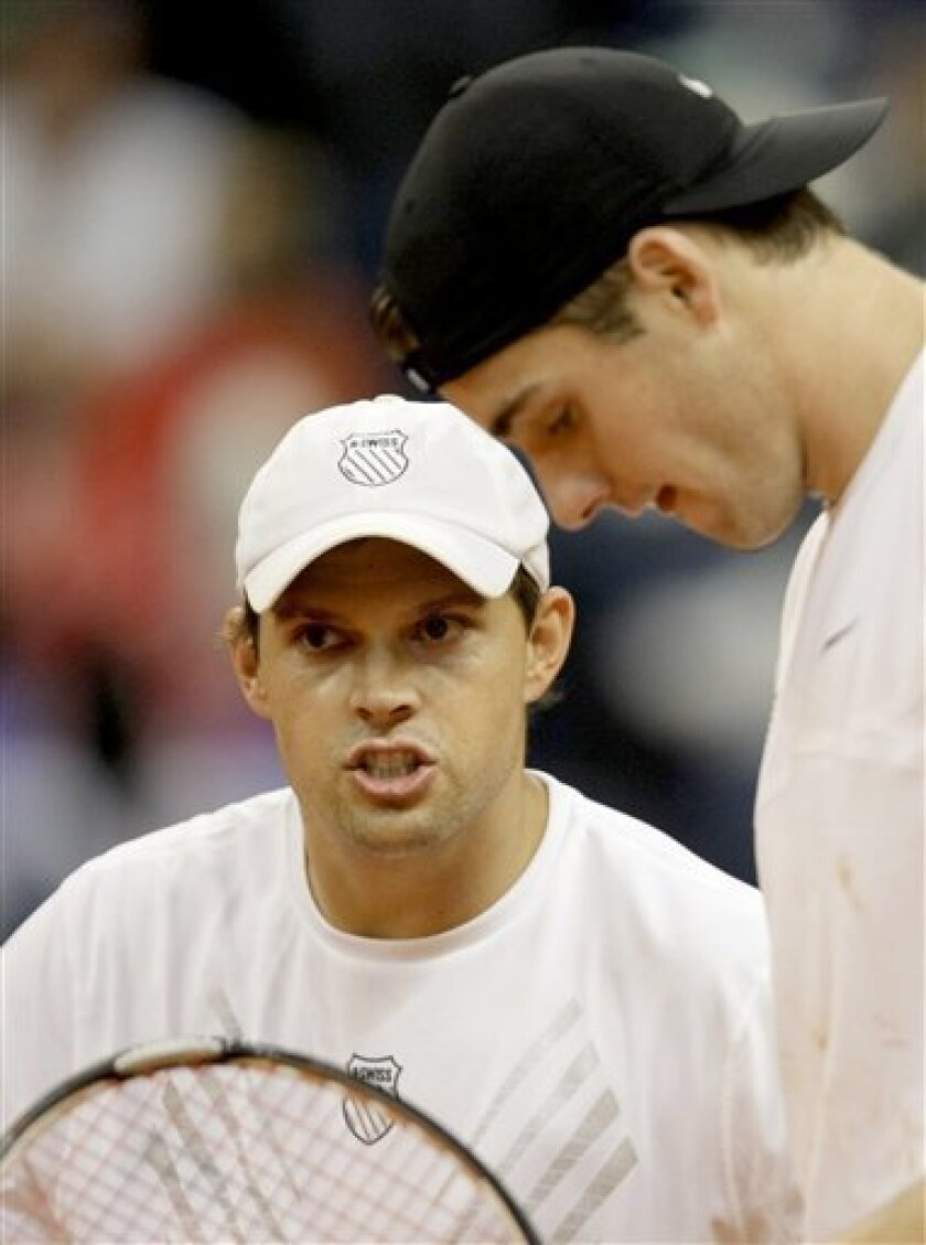 John Isner, right, and Bob Bryan of the US talk tactics during Davis Cup World group first round doubles tennis match against Nenad Zimonjic and Janko Tipsarevic of Serbia, in Belgrade, Serbia, Saturday, March 6, 2010. (AP Photo/Darko Vojinovic)