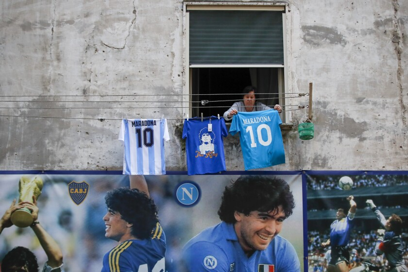 """Una mujer cuelga una pancarta con la frase """"Ciao Diego"""" (""""Adiós, Diego"""") desde un edificio con mural"""