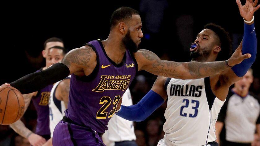LOS ANGELES, CALIF. - NOV. 30, 2018. Lakers forward LeBron James parries with Mavericks guard Wesl