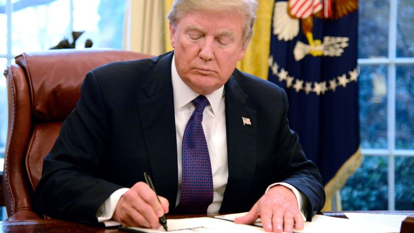 President Trump signs an order on Jan. 23 issuing tariffs on imported solar panels and washing machines.