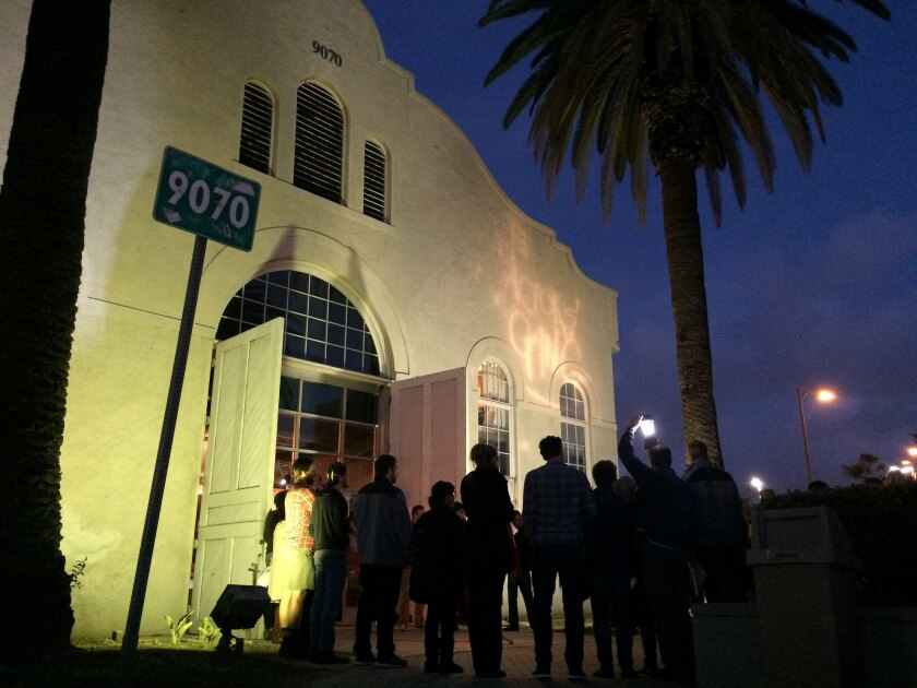 """Members of the Actors' Gang in Culver City gather in front of the theater Thursday night to turn on a """"ghostlight"""" as a gesture of tolerance."""