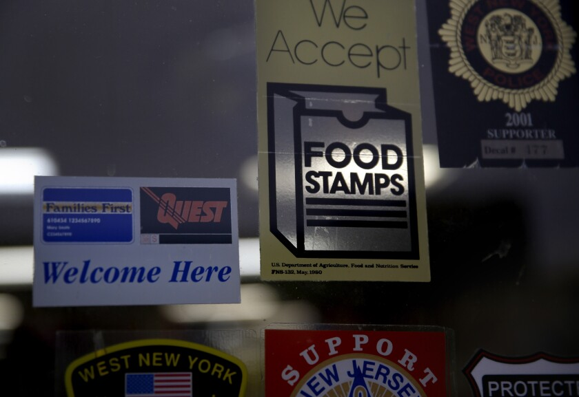 A supermarket displays stickers indicating it accepts food stamps