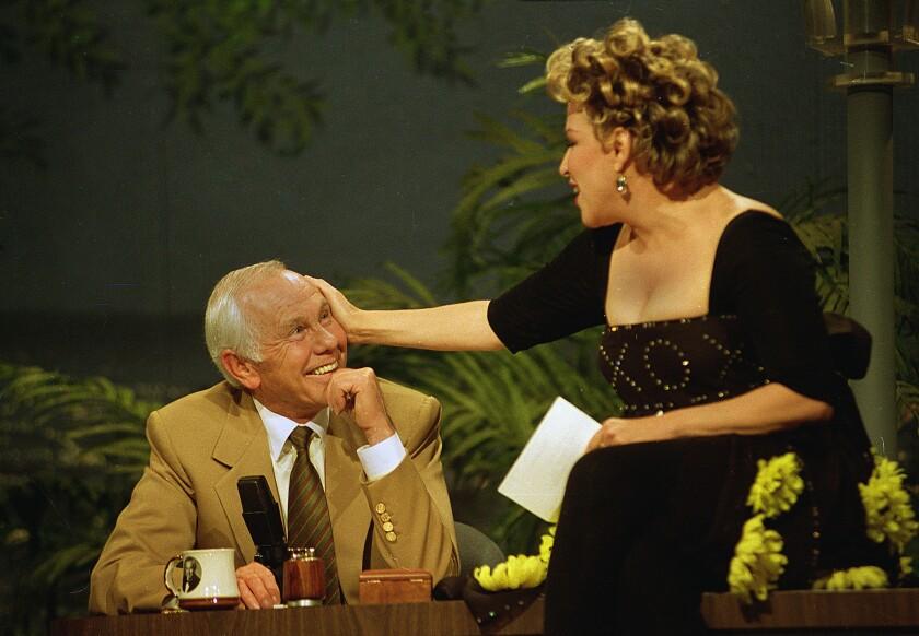 Bette Midler caresses talk show host Johnny Carson.