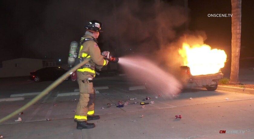 A Vista firefighter begins to battle a car fire Tuesday night in an auto parts store parking lot off East Vista Way.