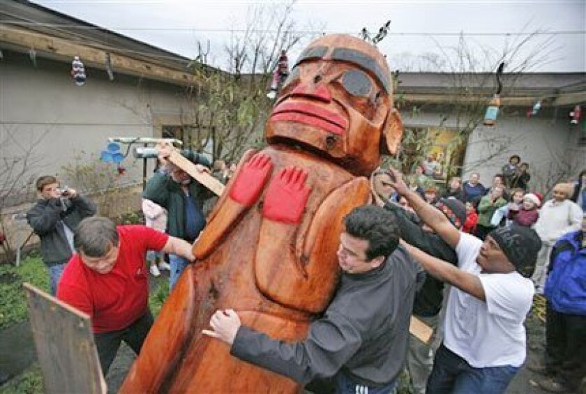 A Haida Watchman totem pole was moved into place yesterday at Parkwood Elementary School in Shoreline, Wash. The 1,200-pound cedar totem pole was carved by a Haida tribe master carver, who worked for several months with students on the project. Paul Joseph Brown / Associated Press