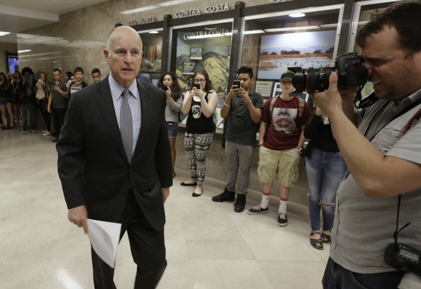 California Gov. Jerry Brown returns to his office Friday after a news conference in which he released his revised 2016-17 state budget plan.