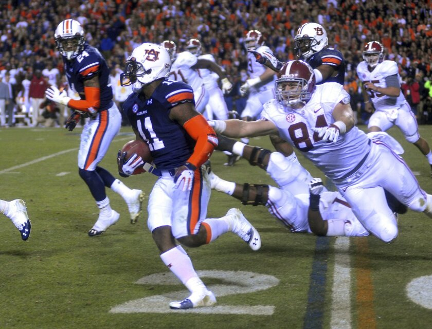 Auburn's Chris Davis runs out of the end zone, breaking the tackle attempt of Alabama's Brian Vogler after a failed Alabama field goal on the final play of the NCAA college football game and runs it back more than 100 yards for the winning touchdown of the Iron Bowl at Jordan-Hare Stadium on Saturday, Nov. 30, 2013, in Auburn, Ala. (AP Photo/The Ledger-Enquirer)