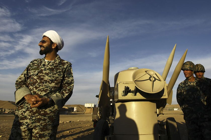 An Iranian clergyman near missiles at an undisclosed location.