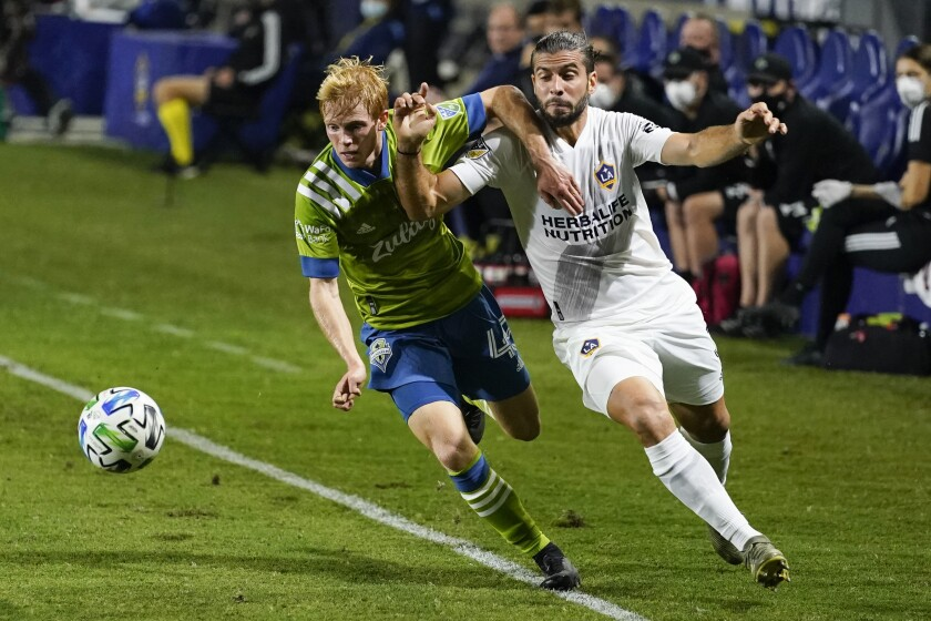 Seattle Sounders midfielder Ethan Dobbelaere and Galaxy defender Emiliano Insua keep the ball in play.