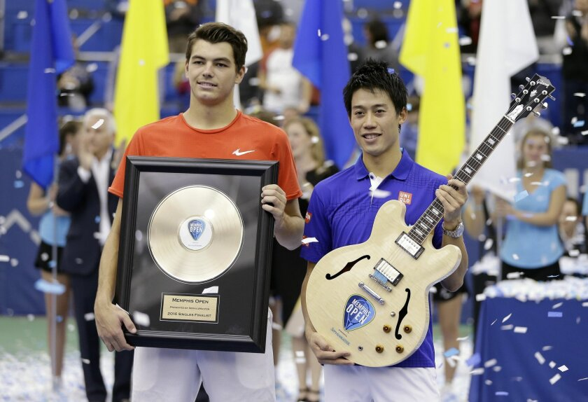 Kei Nishikori, right, of Japan and Taylor Fritz of the United States pose with their trophies after Nishikori beat Fritz in the singles championship at the Memphis Open tennis tournament Sunday, Feb. 14, 2016, in Memphis, Tenn. Nishikori won 6-4, 6-4. (AP Photo/Mark Humphrey)