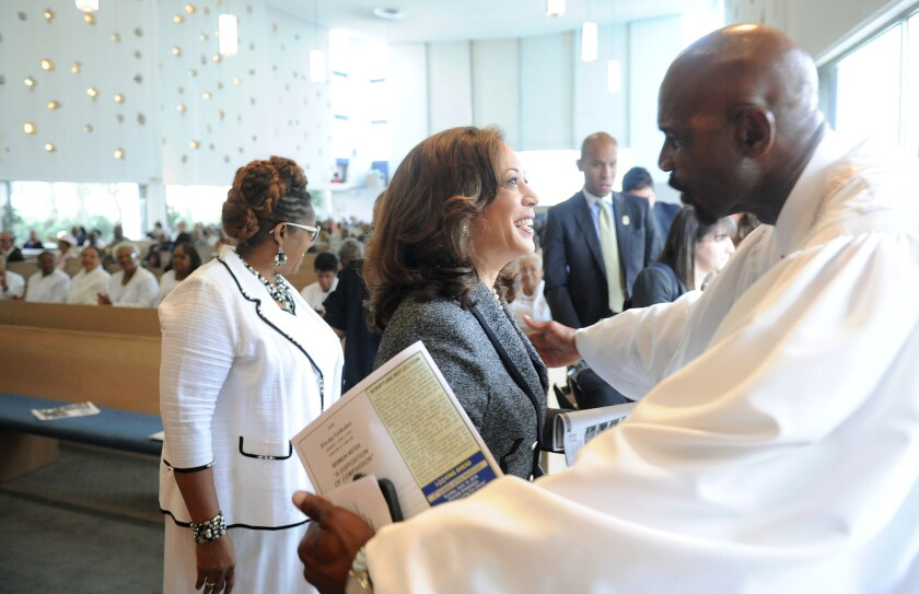 The Rev. Oliver Buie of Holman United Methodist Church in Los Angeles, right, thanks U.S. Senate candidate Kamala Harris for attending a church service Sunday.