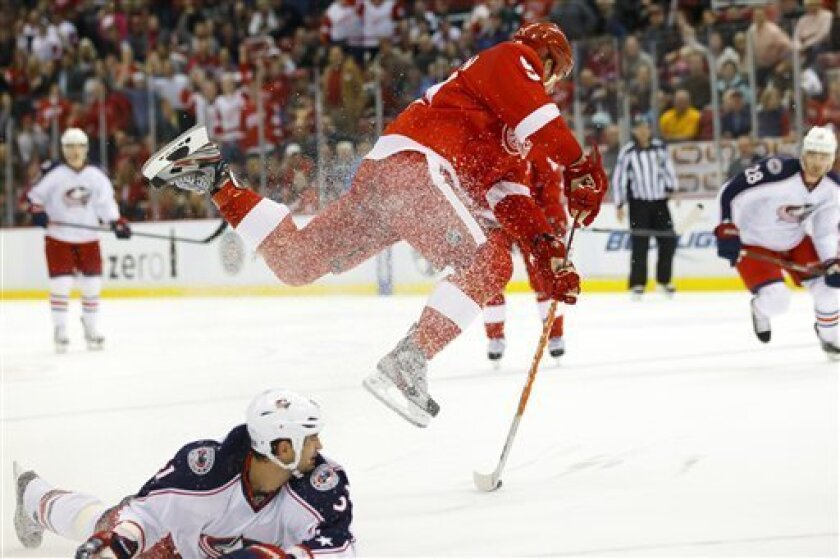 Detroit Red Wings left wing Johan Franzen, top, of Sweden, leaps over Columbus Blue Jackets defenseman Fedor Tyutin, of Russia, as he takes a shot on an open net in the third period of an NHL hockey game in Detroit, on Friday, Oct. 21, 2011. (AP Photo/Rick Osentoski)