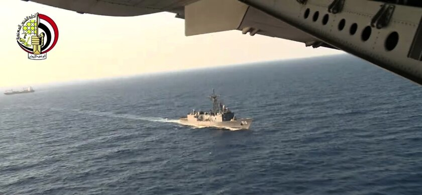 In this Thursday, May 19, 2016 video image released by the Egyptian Defense Ministry, an Egyptian plane flies over an Egyptian ship during the search in the Mediterranean Sea for the missing EgyptAir flight 804 plane which crashed after disappearing from the radar early Thursday morning while carrying 66 passengers and crew from Paris to Cairo. The Egyptian army said Friday, May 20, 2016 that it has found wreckage of the missing Airbus 320 (290 kilometers) north of the city of Alexandria, Egypt. Logo in top left corner of the Egyptian Defense Ministry. (AP Photo/Egyptian Defense Ministry)