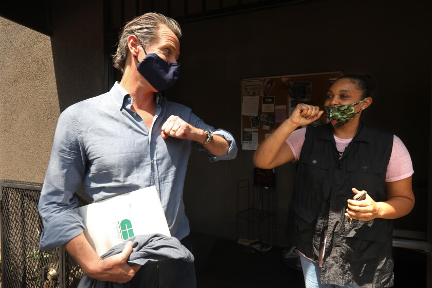 Gov. Gavin Newsom bumps elbows with Los Angeles business owner Candace O'Connor.
