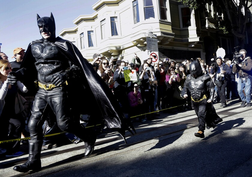 """Miles Scott, dressed as """"Batkid,"""" right, runs with Batman after saving a damsel in distress in San Francisco last year. Miles, 5, was scheduled to appear on the Oscars telecast, but his segment got cut."""
