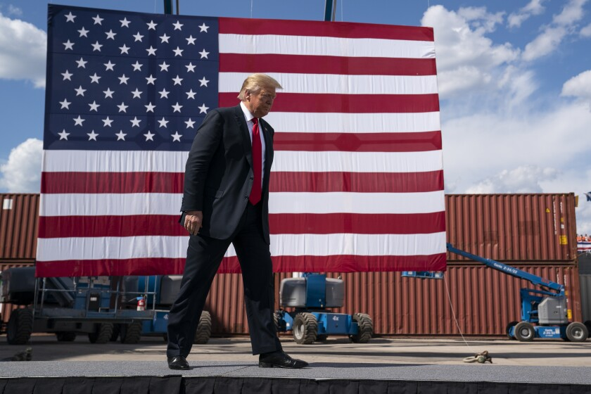 President Trump walks past a large U.S. flag before giving a speech at a shipbuilding firm in Marinette, Wis., on June 25.