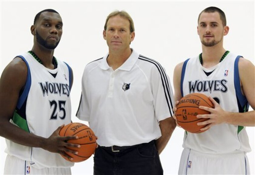 Minnesota Timberwolves new head coach Kurt Rambis, center, poses with veterans Al Jefferson, left, and Kevin Love during NBA basketball media day Monday, Sept. 28, 2009, in Minneapolis. (AP Photo/Jim Mone)