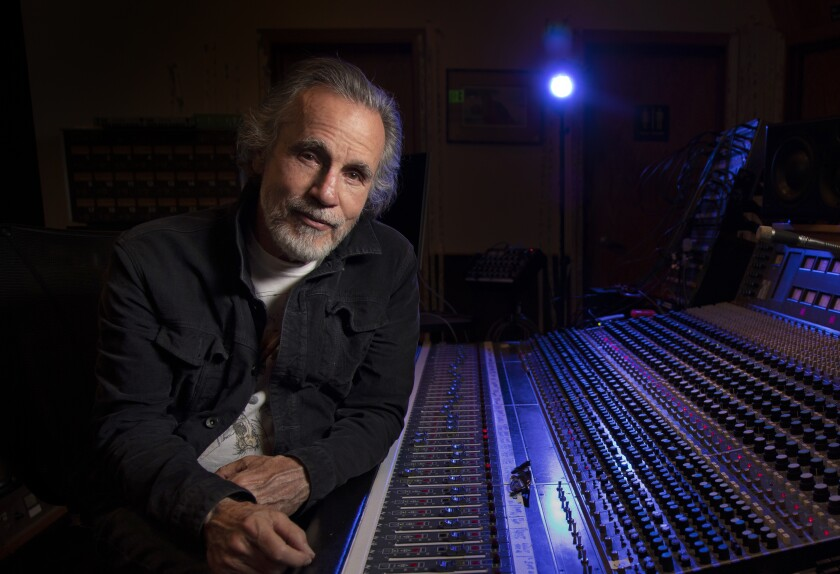 Singer-songwriter Jackson Browne, who has gray hair and beard, sits next to a mixing console in his recording studio