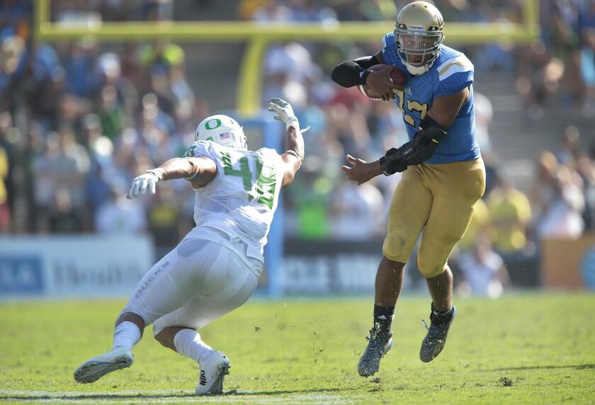 UCLA quarterback Brett Hundley avoids Oregon linebacker Rodney Hardrick during an Oct. 11 game at the Rose Bowl.