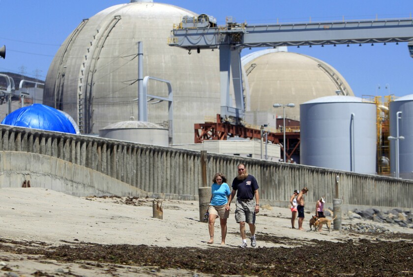 In this 2011 file photo, people walk on the sand near the shuttered San Onofre nuclear power plant in San Clemente.