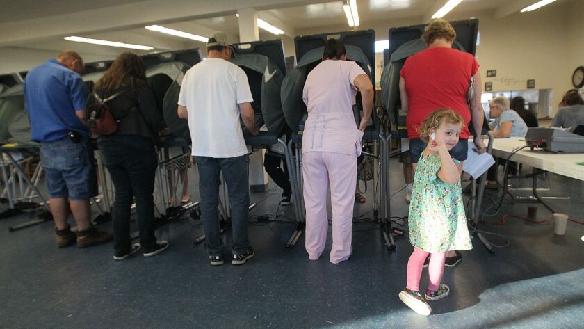 Arabella Ginter, 4, shows off her I Voted sticker as her mom Star Ginter votes at The Lighthouse Chu