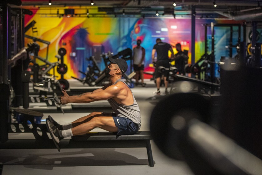A man sits and pulls on a rowing machine in a gym against a backdrop of colorful artwork