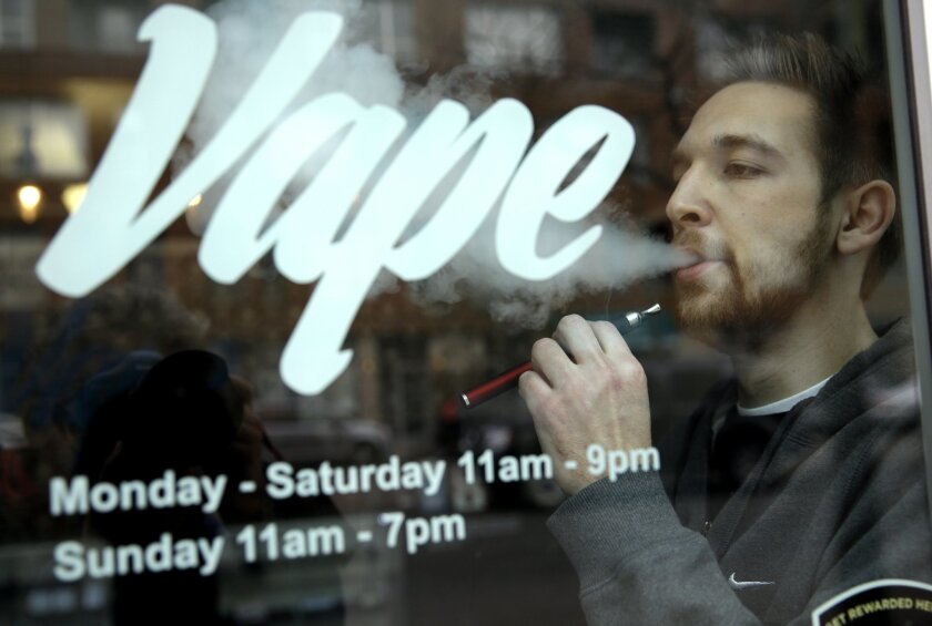 Eric Scheman demonstrates an e-cigarette at Vape store in Chicago, Wednesday, April 23, 2014. The federal government wants to ban sales of electronic cigarettes to minors and require approval for new products and health warning labels under regulations being proposed by the Food and Drug Administra
