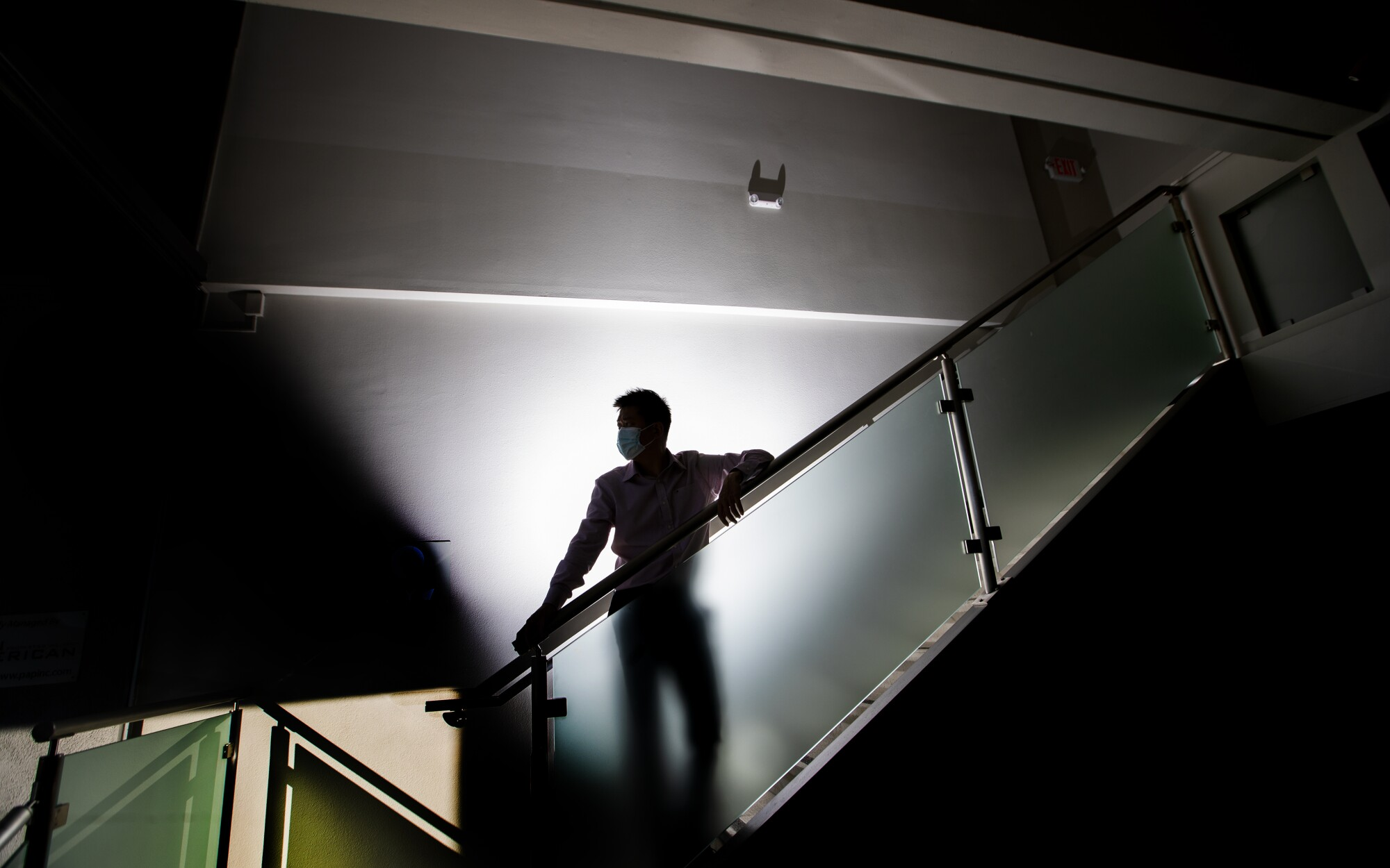 A man in shadows stands on a staircase