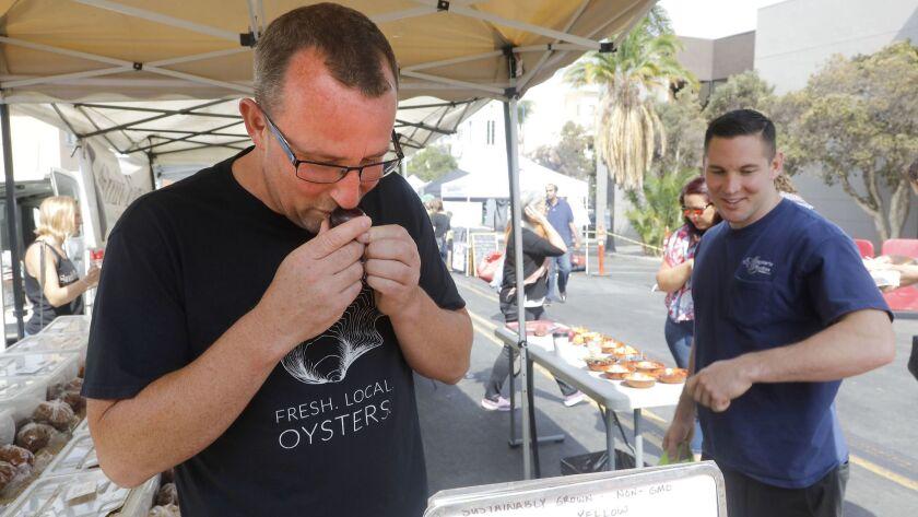 San Diego, CA_7_18_18_|Ironside Chef Jason McLeod, left, smells a plum near Ironside Chef de Cuisine