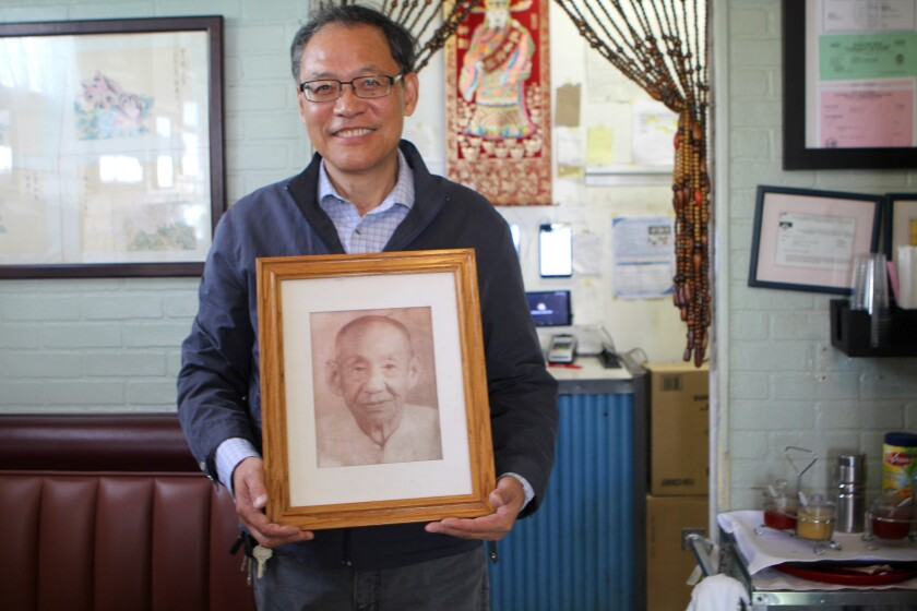Bob Gu, owner of La Jolla's China Chef, poses with the photo of his grandfather, ShanZhuang Gu, that hangs on his restaurant's wall.