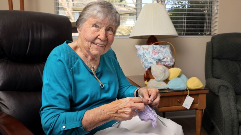 "Pat Anderson knits one of her ""Busters"" wardrobe accessories for breast cancer survivors."